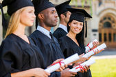 College graduates standing in row — Stock Photo