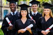 College graduates in graduation gowns — Stock Photo