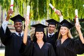 College graduates showing their diplomas — Stock Photo