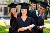 Four college graduates holding diplomas — Stock Photo