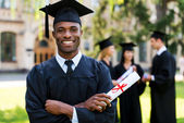 Happy African man in graduation gown — Stock Photo
