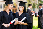 Two happy women in graduation gowns — Stock Photo