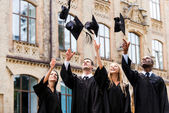 Happy college graduates throwing their mortar boards — Stock Photo