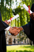 Men in graduation gowns holding diplomas — Foto Stock