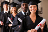 College graduates standing in row and smiling — Stock Photo