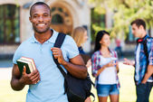 Young African man holding books — Stock Photo