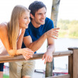 Loving couple leaning at the wooden railing — Stock Photo #51060295