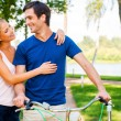 Couple looking at each while man leaning at bicycle — Stock Photo #51061053