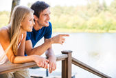 Loving couple leaning at the wooden railing — Stock Photo