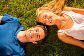 Couple lying on the green grass — Stock Photo