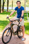 Young man riding bicycle in park — Stock Photo