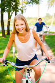 Woman riding  bicycle while boyfriend riding bike in background — Stock Photo