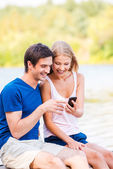 Couple sitting at the quayside and looking at mobile phone — Stock Photo