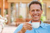 Mature man drinking coffee and smiling — Stock Photo