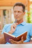 Thoughtful mature man holding note pad — Stock Photo