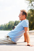 Mature man sitting at the quayside — Stock Photo