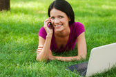 Woman talking on phone lying in grass with laptop — Stock Photo