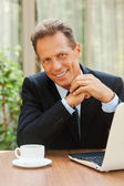 Mature man in formalwear sitting at the table with laptop — Stock Photo