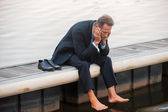 Depressed mature businessman at the quayside — Stock Photo