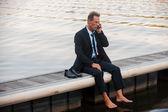 Empresário falando no celular no cais — Fotografia Stock