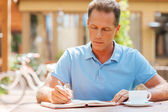 Mature man writing something in his note pad outdoors — Stock Photo