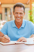 Man writing something in his note pad outdoors — Stock Photo