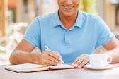 Confident mature man writing something outdoors — Stock Photo