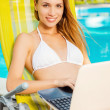 Woman in white bikini sitting with laptop — Stock Photo #51142439