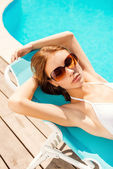 Woman in white bikini relaxing in deck chair — Stockfoto