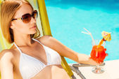 Woman in white bikini holding glass with cocktail — Stock Photo