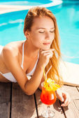 Woman in white bikini lying by the poolside — Stockfoto