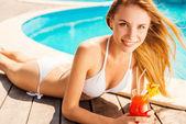Woman in white bikini lying by the poolside — Stockfoto