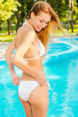 Woman in white bikini adjusting panties — Stock Photo