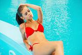 Woman in red bikini relaxing by the pool — Foto Stock