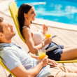 Couple holding cocktails by the pool — Stock Photo