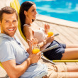 Couple sitting at the deck chairs by the pool — Stock Photo #51255937