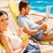 Couple sitting at the deck chairs by the pool — Stock Photo #51255943