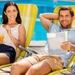Couple relaxing at the deck chairs by the pool — Stock Photo #51255955