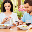 Young couple typing on smart phones in restaurant — Stock Photo