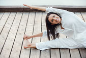Woman in white clothing performing yoga — Stock Photo