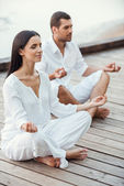Young couple meditating — Stock Photo