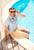 Man sitting by the pool and adjusting sunglasses — Stock Photo