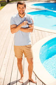 Man in polo shirt standing by the pool — Photo