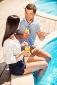 Couple sitting poolside and talking — Stock Photo