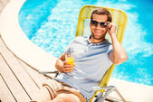 Man sitting at deck chair with glass of juice — Stock Photo
