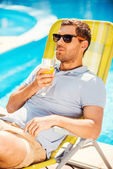 Man sitting at the deck chair and drinking juice — Stock Photo
