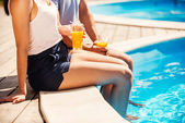 Couple sitting poolside and drinking cocktails — Stock Photo