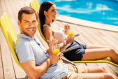 Couple sitting at the deck chairs by the pool — Stock Photo