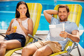 Couple relaxing at the deck chairs by the pool — Stock Photo