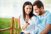 Woman showing mobile phone to boyfriend — Stockfoto